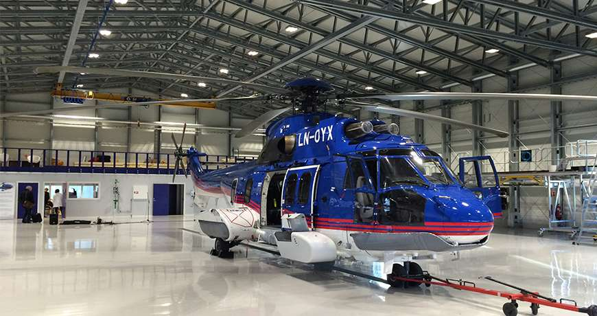 Aircraft Hangar with large blue and white helicopter parked inside in a dry and easy to access place